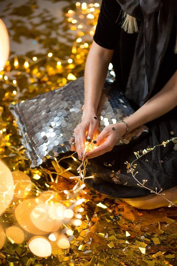 Η κατάπληξη της χαριτωμένης κυρίας που γιορτάζει τη νέα γιορτή γενεθλίων έτους, που θέτει στο χρυσό λάμπει υπόβαθρο και ρίψη του  στοκ φωτογραφία με δικαίωμα ελεύθερης χρήσης