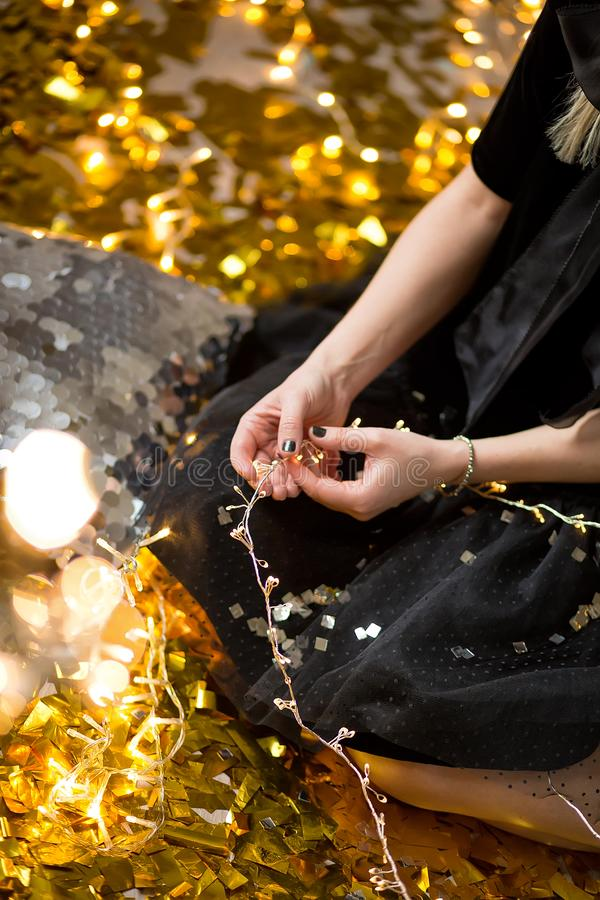 Η κατάπληξη της χαριτωμένης κυρίας που γιορτάζει τη νέα γιορτή γενεθλίων έτους, που θέτει στο χρυσό λάμπει υπόβαθρο και ρίψη του  στοκ εικόνες