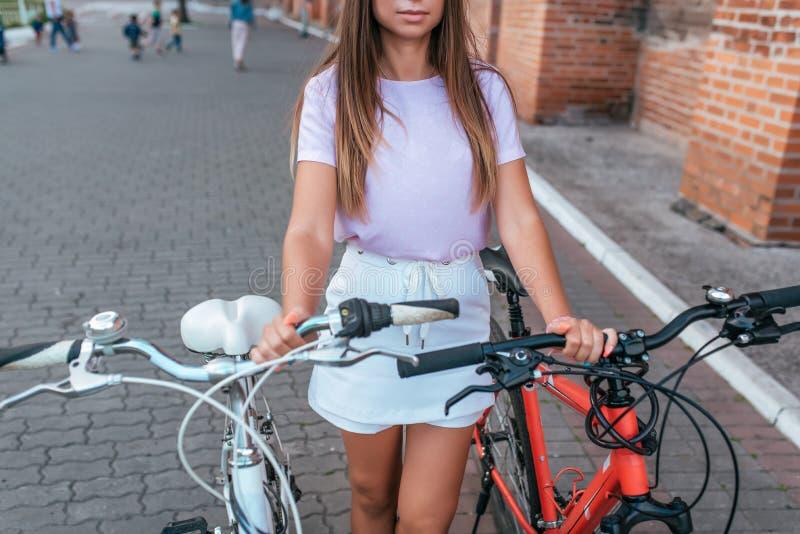 Η κινηματογράφηση σε πρώτο πλάνο ενός κόκκινου και άσπρου ποδηλάτου, το κορίτσι κρατά σταθμευμένος πίσω από το πλαίσιο Το καλοκαί στοκ φωτογραφίες με δικαίωμα ελεύθερης χρήσης