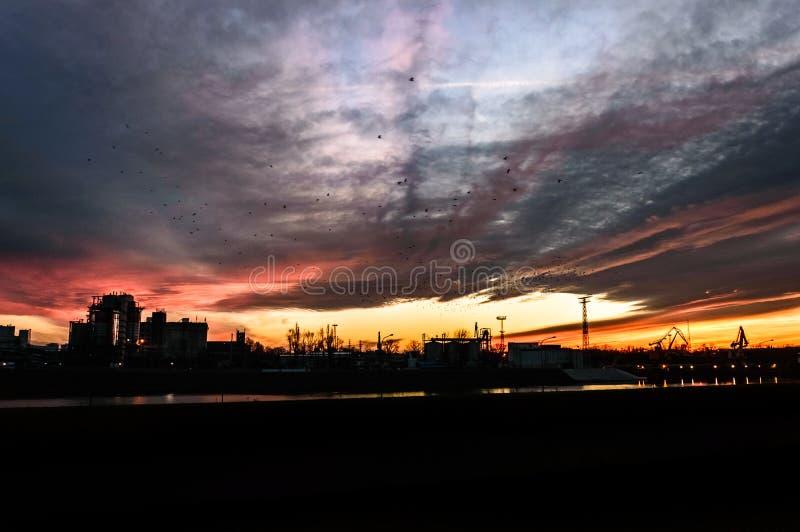 Η κοίτη του ποταμού στη ζώνη εκφόρτωσης άνθρακα στις εγκαταστάσεις θερμικής παραγωγής ενέργειας, ηλιοβασίλεμα στοκ φωτογραφία