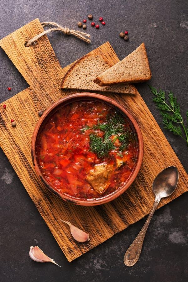 Η κόκκινη σούπα με borsch βόειου κρέατος εξυπηρέτησε σε ένα πιάτο αργίλου με το ψωμί σίκαλης σε έναν τέμνοντα πίνακα, τοπ άποψη Ρ στοκ εικόνα