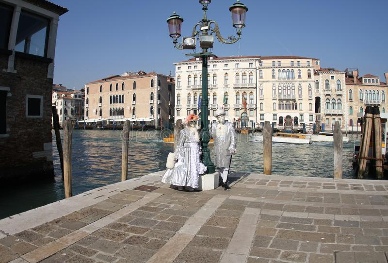 Η κυρία και ο κύριος θέτουν σε ένα ασημένιο κοστούμι Βενετία καρναβάλι 2019 στοκ φωτογραφία