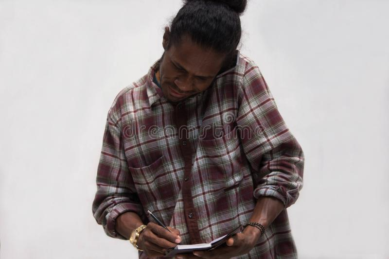 Η λήψη μαύρων σημειώνει μιλώντας στα τηλέφωνα, νέα συζήτηση ατόμων της Παπούας με το smartphone ενώ γράψτε στις σημειώσεις στοκ εικόνα με δικαίωμα ελεύθερης χρήσης