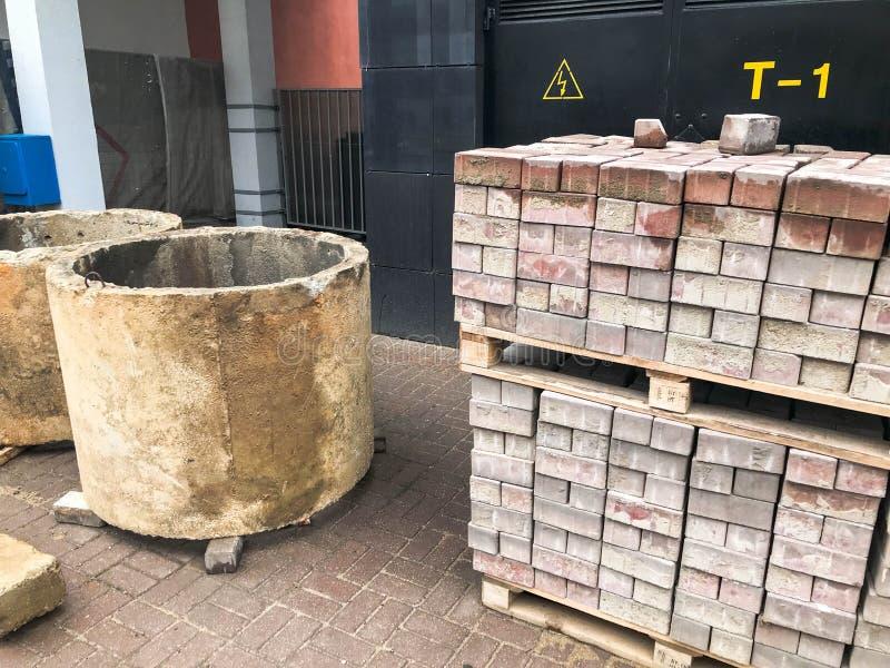 Η μεγάλη στρογγυλή συγκεκριμένη πέτρα τσιμέντου περιβάλλει τα φρεάτια δαχτυλιδιών και τα κεραμίδια πετρών επίστρωσης στα ξύλινα p στοκ εικόνα με δικαίωμα ελεύθερης χρήσης