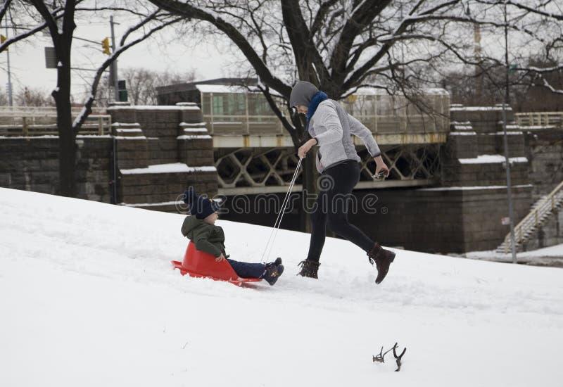 Η μητέρα βοηθά το έλκηθρο γύρου παιδιών της στο χιόνι στο πάρκο της Νέας Υόρκης Bronx στοκ εικόνες με δικαίωμα ελεύθερης χρήσης