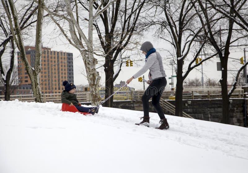 Η μητέρα βοηθά το έλκηθρο γύρου παιδιών της στο χιόνι στο πάρκο της Νέας Υόρκης Bronx στοκ φωτογραφία