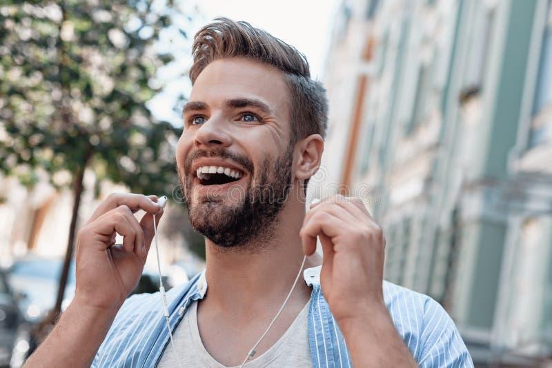 Η μουσική είναι ένα ξέσπασμα της ψυχής Ο νεαρός άνδρας ακούει τη μουσική μέσω των ακουστικών περπατώντας γύρω από την πόλη στοκ φωτογραφία με δικαίωμα ελεύθερης χρήσης