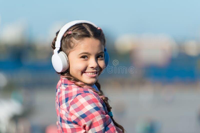 Η μουσική δίνει τη μεγάλη ευχαρίστησή της Χαριτωμένο παιδί με την ασύρματη κάσκα Μικρό παιδί που φορά τα στερεοφωνικά ακουστικά Λ στοκ εικόνα