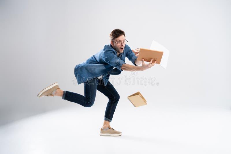 Η μπροστινή άποψη του πηγαίνοντας όμορφου ατόμου φέρνει έναν σωρό των βιβλίων περπάτημα του νέου τύπου πέρα από το λευκό Ο σπουδα στοκ φωτογραφία με δικαίωμα ελεύθερης χρήσης