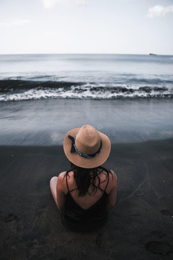 Η νέα γυναίκα κάθεται στη μαύρη παραλία άμμου στοκ φωτογραφίες
