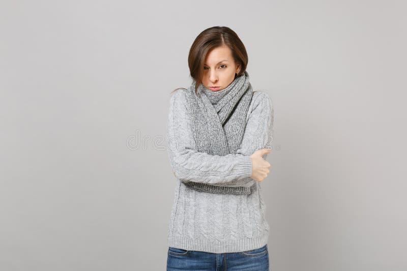 Η νέα γυναίκα στο γκρίζο πουλόβερ, μαντίλι που αισθάνεται τα κρύα χέρια λαβής δίπλωσε απομονωμένος στο γκρίζο υπόβαθρο τοίχων στο στοκ φωτογραφία με δικαίωμα ελεύθερης χρήσης