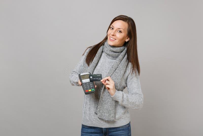 Η νέα γυναίκα στο πουλόβερ, ασύρματο σύγχρονο τερματικό πληρωμής τραπεζών λαβής μαντίλι στη διαδικασία, αποκτά τις πληρωμές με πι στοκ εικόνα