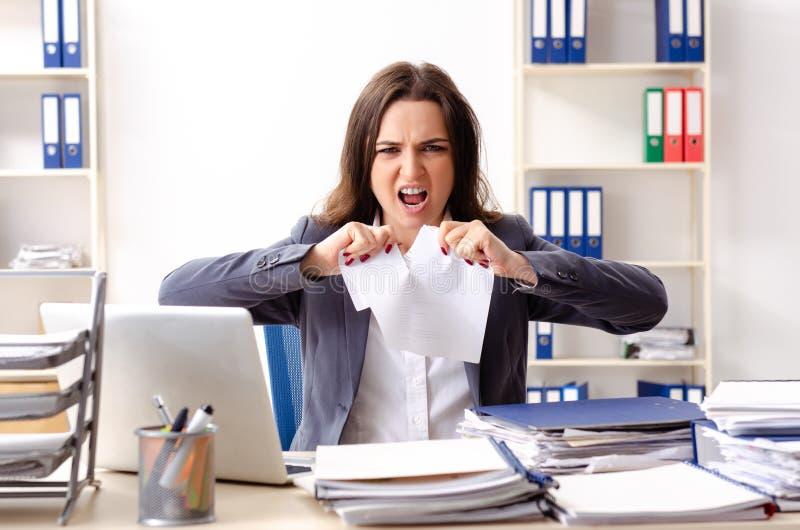 Η νέα γυναίκα υπάλληλος δυστυχισμένος με την υπερβολική εργασία στοκ εικόνα με δικαίωμα ελεύθερης χρήσης