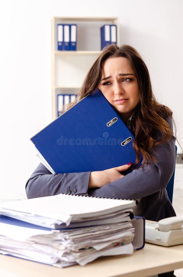 Η νέα γυναίκα υπάλληλος δυστυχισμένος με την υπερβολική εργασία στοκ φωτογραφία