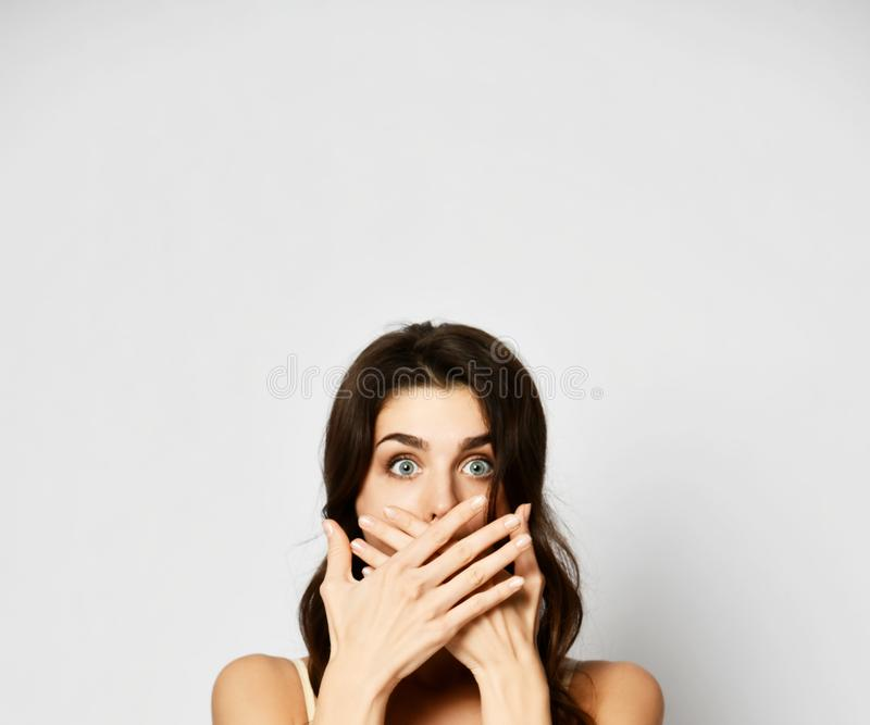 Η νέα όμορφη γυναίκα καλύπτει το στόμα της και με τα δύο χέρια όπως αυτή είναι φοβησμένη πολύ ή ανέτρεψε ακριβώς ένα μεγάλο μυστι στοκ φωτογραφία με δικαίωμα ελεύθερης χρήσης