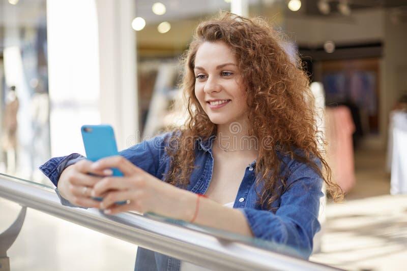 Η νέα σγουρή ομορφιά στέκεται στη λεωφόρο αγορών, τηλέφωνο λαβής, τηλέφωνο σε ευχάριστη περίπτωση χρώματος Το πρόσωπο εκφράζει τη στοκ φωτογραφία με δικαίωμα ελεύθερης χρήσης