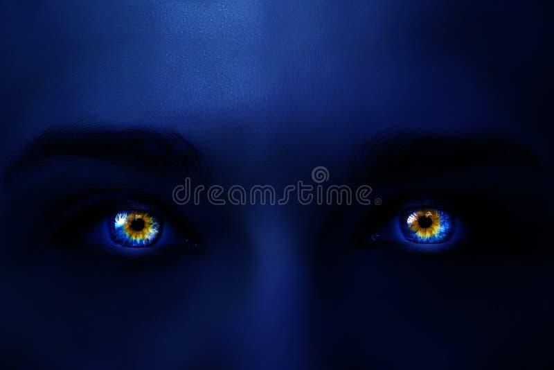 Η δημιουργική φωτογραφία του προσώπου μιας γυναίκας με το ελαφρύ σκούρο μπλε χρώμα νέου και τα καμμένος πολύχρωμα μάτια με μυστήρ στοκ φωτογραφία