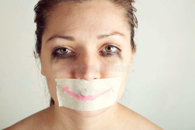 Η δυστυχισμένη γυναίκα με το τύλιγμα του στόματός της από την κολλητική ταινία χρωμάτισε το χαμόγελο στοκ φωτογραφία
