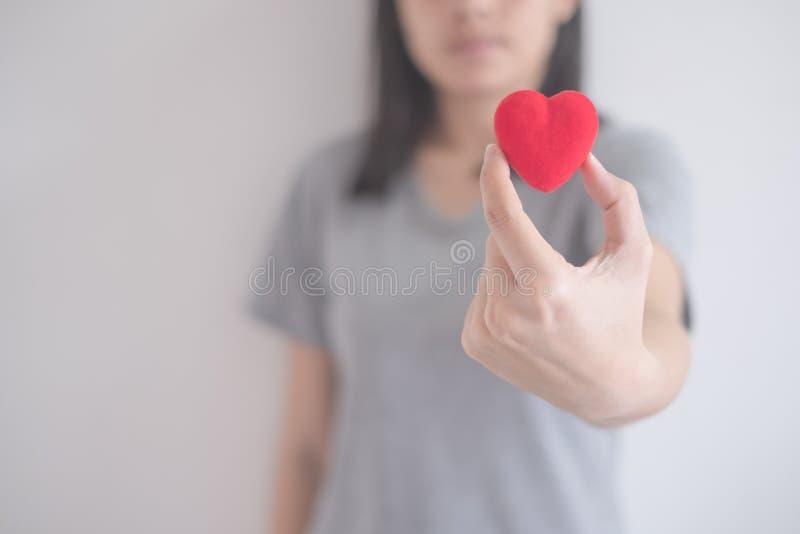 Η όμορφη ασιατική γυναίκα παρουσιάζει κόκκινη καρδιά σε ένα άσπρο υπόβαθρο με το διάστημα αντιγράφων στοκ εικόνα με δικαίωμα ελεύθερης χρήσης