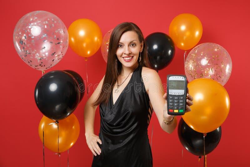 Η όμορφη γυναίκα στο μαύρο φορεμάτων τερματικό πληρωμής τραπεζών λαβής ασύρματο σύγχρονο στη διαδικασία, αποκτά τις πληρωμές με π στοκ εικόνες