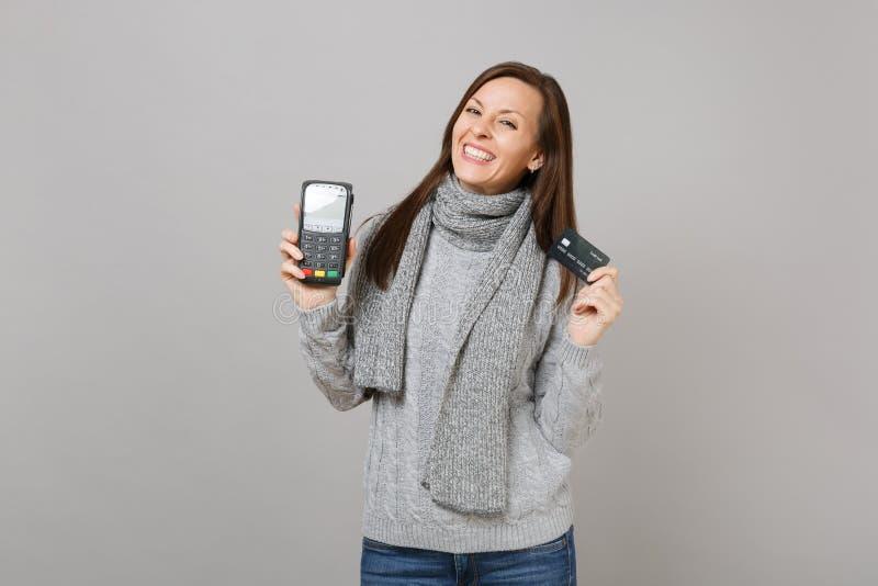 Η όμορφη γυναίκα στο πουλόβερ, ασύρματο σύγχρονο τερματικό πληρωμής τραπεζών λαβής μαντίλι στη διαδικασία, αποκτά τις πληρωμές με στοκ φωτογραφίες με δικαίωμα ελεύθερης χρήσης