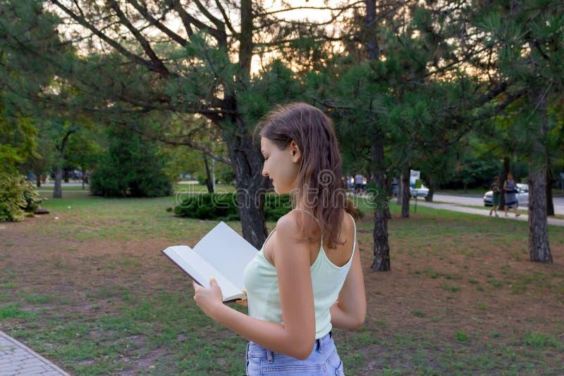 Η όμορφη γυναίκα σπουδαστής περπατά στο πάρκο και διαβάζει ένα βιβλίο στοκ εικόνες με δικαίωμα ελεύθερης χρήσης