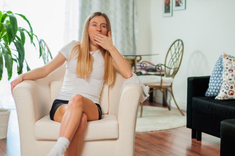 Η όμορφη γυναίκα τρύπησε στο σπίτι το χασμουρητό που κουράζεται καλύπτοντας το στόμα με το χέρι στοκ εικόνα με δικαίωμα ελεύθερης χρήσης
