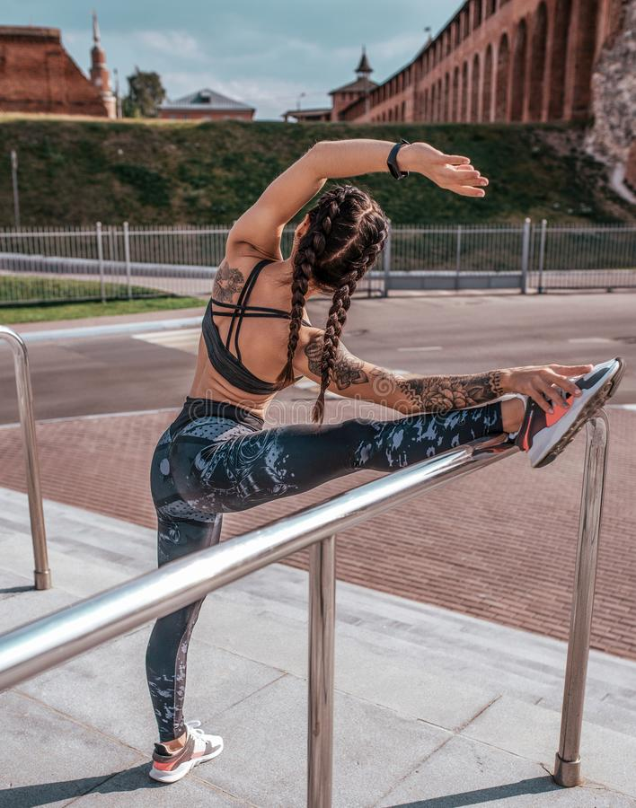 Η όμορφη νέα γυναίκα στις δερματοστιξίες, θερινή πόλη, τεντώνει τους μυς του ποδιού πριν από ένα workout sportswear, περικνημίδες στοκ φωτογραφία με δικαίωμα ελεύθερης χρήσης
