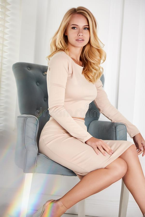 Η όμορφη προκλητική ξανθή γυναίκα κάθεται το τέλειο πρόσωπο καρεκλών που το καλλυντικό πρότυπο ύφους τρίχας hairdo σαλονιών ομορφ στοκ εικόνες