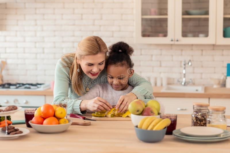 Η σγουρή κόρη που απολαμβάνει το μαγείρεμα με την ενθαρρύνει mom στοκ εικόνες