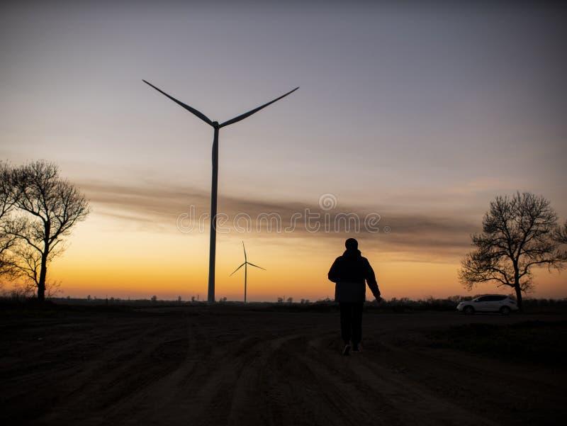 Η σκιαγραφία ενός ατόμου πηγαίνει στο ηλιοβασίλεμα στην κατεύθυνση των ανεμοστροβίλων στοκ φωτογραφία με δικαίωμα ελεύθερης χρήσης
