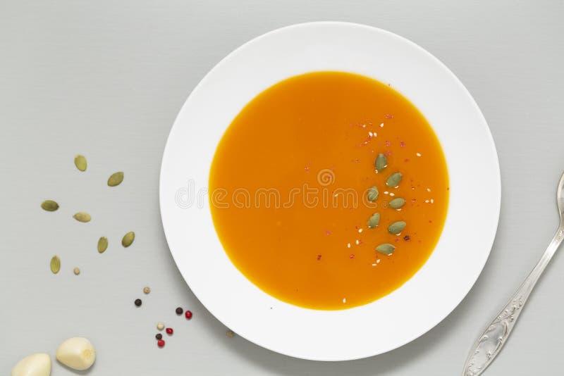 Η σούπα κολοκύθας με τα χορτάρια, την κρέμα και τους σπόρους κολοκύθας εξυπηρέτησε στο άσπρο κύπελλο Εποχιακά τρόφιμα φθινοπώρου  στοκ εικόνες