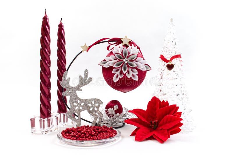 Η σύνθεση των διακοσμήσεων Χριστουγέννων με τον ασημένιο τάρανδο μπροκάρ και τα κόκκινα κεριά στοκ εικόνες