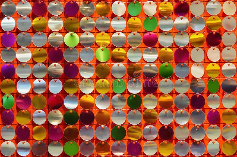 Η σύσταση των disk-shaped λαμπρών μετάλλων διακοσμεί τα τσέκια και τις πούλιες σε ένα ζωηρόχρωμο διακοσμητικό υπόβαθρο με χάντρες στοκ φωτογραφία με δικαίωμα ελεύθερης χρήσης