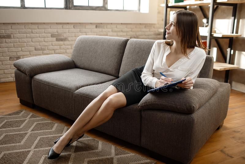 Η στοχαστική νέα γυναίκα κάθεται στον καναπέ στο δωμάτιο γραφείων Κοιτάζει στο παράθυρο και το περιοδικό λαβής Χαλάρωση πασπαλίζο στοκ εικόνες