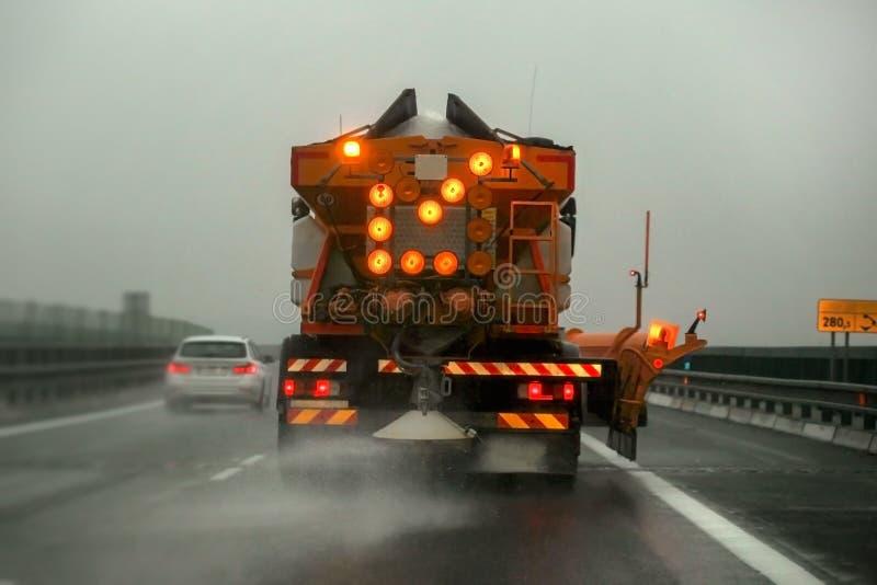 Η συντήρηση εθνικών οδών gritter μεταφέρει το αποψύχοντας άλας διάδοσης, στον καλυμμένο πάγος δρόμο ασφάλτου με φορτηγό κατά τη δ στοκ φωτογραφίες
