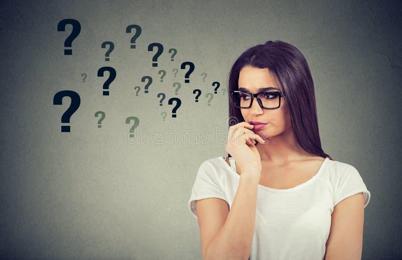 Η ταραγμένη σκεπτόμενη γυναίκα που επιδιώκει μια λύση που φαίνεται ανησυχημένη έχει πολλές ερωτήσεις στοκ φωτογραφίες