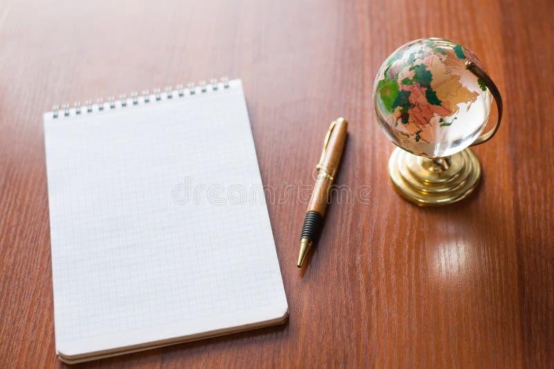 Η τοπ άποψη της κενής Λευκής Βίβλου σημειωματάριων και ο κόσμος σφαιρών χαρτογραφούν στο ξύλινο υπόβαθρο με το διάστημα για το μή στοκ εικόνες