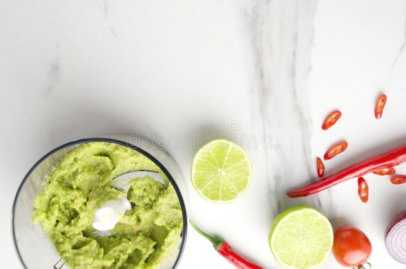 Η τοπ άποψη του κύπελλου με το νόστιμο guacamole με το πιπέρι τσίλι και οι ντομάτες εξυπηρέτησαν στον άσπρο πίνακα στην κουζίνα,  στοκ φωτογραφία