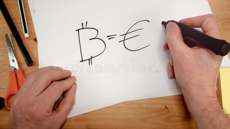 Η τοπ άποψη, το χέρι ενός επιχειρηματία επισύρει την προσοχή το σύμβολο του bitcoin και του ευρώ σε ένα φύλλο του εγγράφου, ιδανι στοκ εικόνες