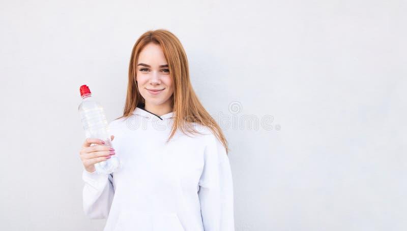 Η φίλαθλη νέα γυναίκα σε μια άσπρη μπλούζα στέκεται στο υπόβαθρο ενός άσπρου τοίχου στοκ εικόνες με δικαίωμα ελεύθερης χρήσης