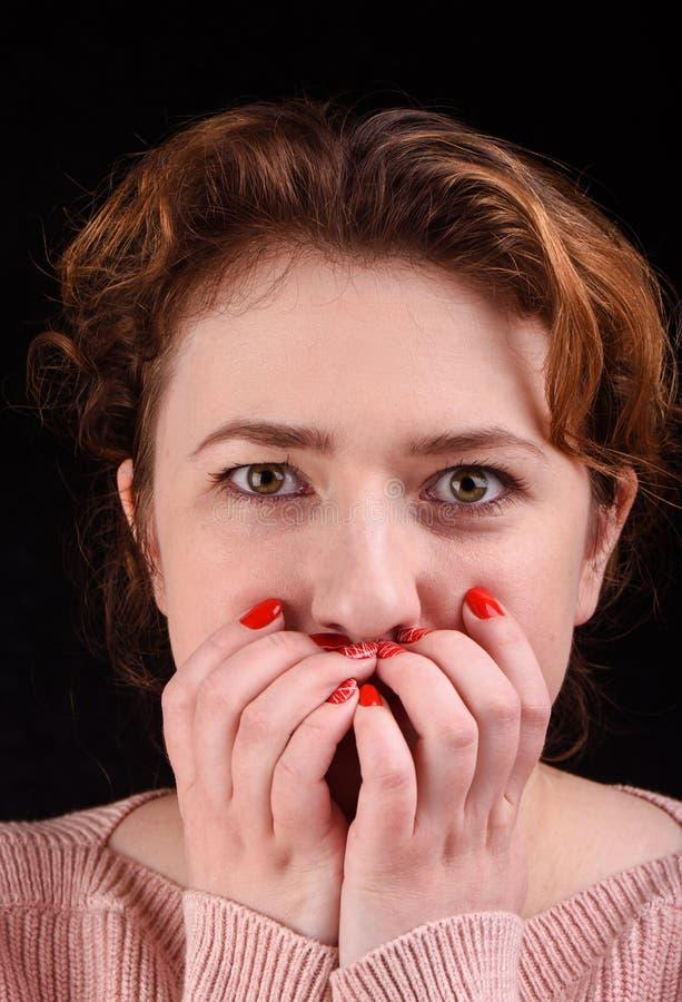 Η φωτογραφία κινηματογραφήσεων σε πρώτο πλάνο του όμορφου κοριτσιού καλύπτει το στόμα της με τους φοίνικες και φαίνεται ευθεία Έν στοκ φωτογραφία με δικαίωμα ελεύθερης χρήσης