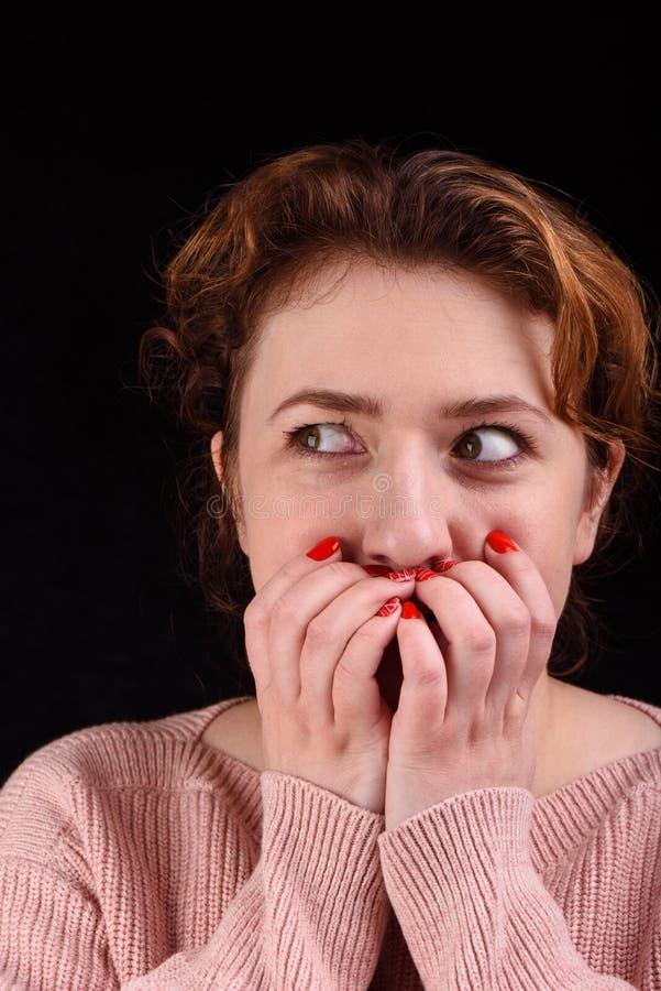 Η φωτογραφία κινηματογραφήσεων σε πρώτο πλάνο του όμορφου κοριτσιού καλύπτει το στόμα της με τους φοίνικες και κοιτάζει στην πλευ στοκ εικόνες