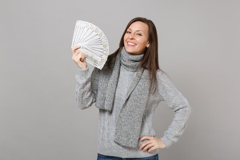 Η χαμογελώντας νέα γυναίκα στο γκρίζο πουλόβερ, δέσμη μερών λαβής μαντίλι των τραπεζογραμματίων δολαρίων εξαργυρώνει τα χρήματα π στοκ εικόνα με δικαίωμα ελεύθερης χρήσης