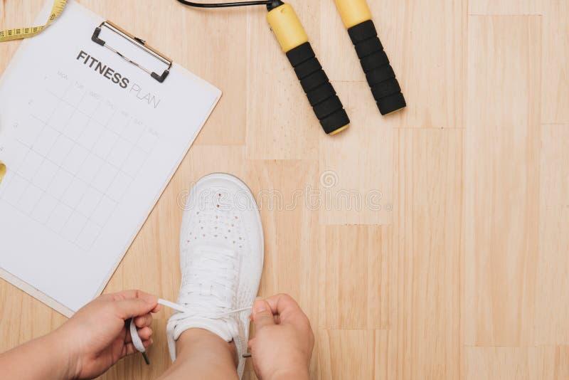 Η υπερυψωμένη άποψη της γυναίκας δίνει τα δένοντας παπούτσια με τους αθλητικούς εξοπλισμούς στο ξύλινο υπόβαθρο στοκ εικόνες με δικαίωμα ελεύθερης χρήσης