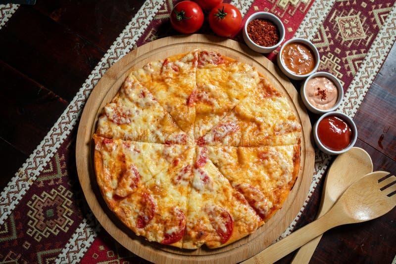 Η πίτσα που βρίσκεται σε ένα ξύλινο πιάτο σε ένα τραπεζομάντιλο με τα εθνικά σχέδια, είναι έπειτα τέσσερις σάλτσες και τρεις ντομ στοκ εικόνα με δικαίωμα ελεύθερης χρήσης