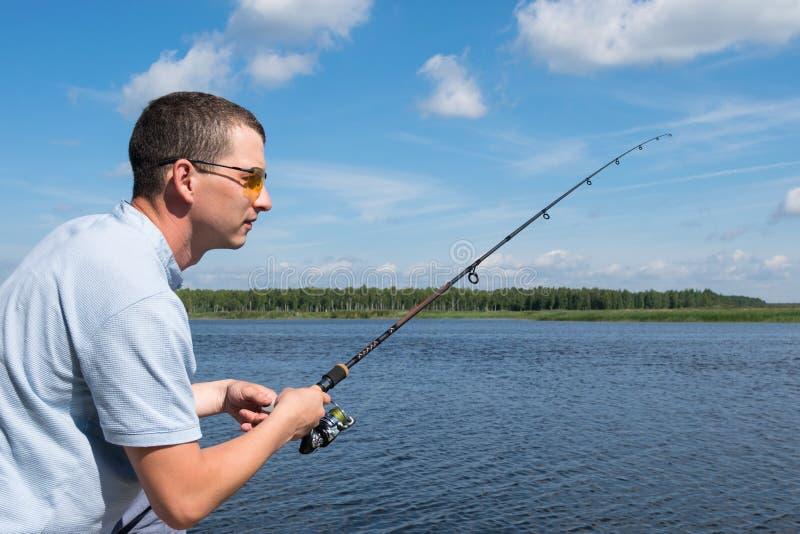 Η πλάγια όψη, ένα άτομο με τα γυαλιά αλιεύει για την περιστροφή στο ανοικτό νερό στοκ φωτογραφία