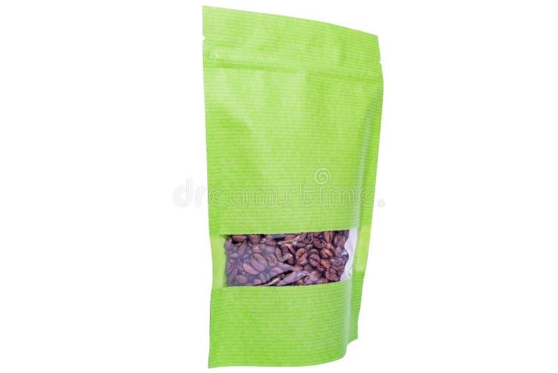Η Πράσινη Βίβλος doypack στέκεται επάνω τη σακούλα με το φερμουάρ λωρίδων που γεμίζουν με τα φασόλια καφέ στο άσπρο υπόβαθρο στοκ φωτογραφίες