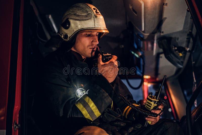 Η πυροσβεστική έφθασε στη νύχτα Συνεδρίαση πυροσβεστών στο πυροσβεστικό όχημα και ομιλία στο ραδιόφωνο στοκ εικόνες