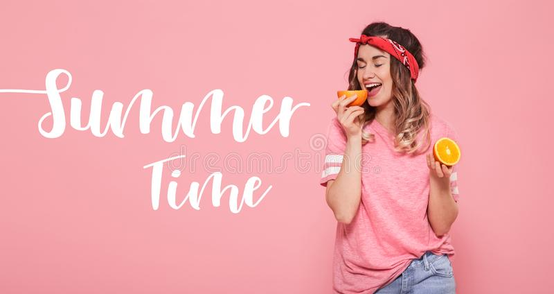 Θερινός χρόνος επιγραφής Το όμορφο νέο κορίτσι στη ρόδινη μπλούζα, κρατά το αστείο πορτοκάλι στο ρόδινο υπόβαθρο στοκ φωτογραφία με δικαίωμα ελεύθερης χρήσης